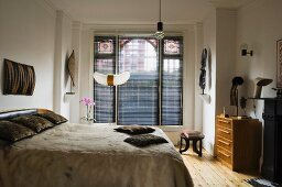 Double bed with fur bedspread and window in background with closed louver blinds in ethnic ambiance
