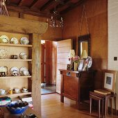 Open-plan dining area with crockery on rustic shelving and cabinet against wood-panelled wall