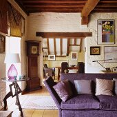 Purple sofa with scatter cushions next to side table in rustic interior with wood-beamed ceiling and view of dining area through wide open doorway