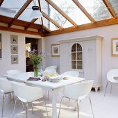 Modern, white shell chairs at dining table in front of farmhouse cupboard in extension with wood and glass roof structure