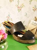 Old ladies shoe used as a pencil holder on a green surface in front of floral wallpaper