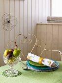 Kleine Obstschale und ein Gedeck auf einem Tisch mit grüner Tischdecke
