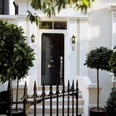 Wrought iron gate and small bay trees in front of traditional, English house