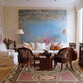 Large, abstract painting behind seating area with loose-covered sofa and classic wicker armchairs in elegant ambiance