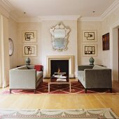 Velvet sofas on star-patterned rug in front of fireplace and ornate, antique mirror and modern artworks on walls