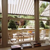 View through sash windows onto terrace with set table below striped awning