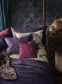 Bedroom in the Bohemian Look: bed with decorative pillows in front of a wall with patterned wallpaper
