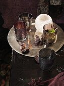 Tray with dried dates, glasses and tea light holders on a dark table
