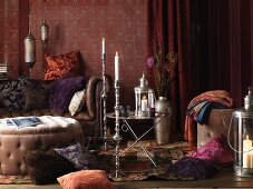 Living room in the Bohemian Look: pillows on the floor and on a leather sofa, upholstered table, side table and silver candlesticks
