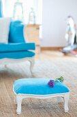 Blauer antiker Armstuhl und Hocker mit Lavendelblüten auf Teppich
