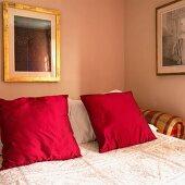 Doppelbett mit roten Kissen und Tagesdecke (Ausschnitt)