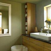 Badezimmer mit grünen Wänden, Holzmöbeln, Waschbecken vor dem Fenster, WC und Wandspiegel