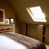 Schlafzimmer im Dachgeschoss mit grünen Wänden, stoffbezogenem Einbauschrank, Bett und Dachfenster