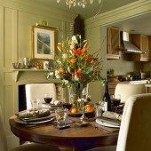 Gedeckter Tisch mit Blumenstrauss und Rotwein in einem Landhaus