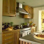 Küche im Landhausstil mit pastellgrünen Wänden, Holzmöbeln, Dunstabzugshaube über dem Herd und Mittelblock mit Spülbecken