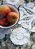 Crocheted doilies tied together as mat underneath bowl of apples