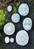 Pebbles decorated with various lace doilies on mossy tree trunk