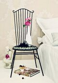 Pink roses of variety ' Yves Piaget' on figurine of woman & in vase on romantic metal chair next to bed