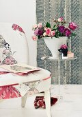 Bouquet of roses in conical vase on small plexiglass table next to chair upholstered in fabric with fifties pattern