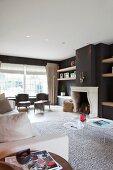 Geräumiges Wohnzimmer mit Sofa auf weißem Teppich und eleganten Sesseln am Fenster in traditionellem Ambiente mit offenem Kamin