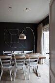Blick durch offene Tür auf weisslackierte Küchenstühle und rustikalem Tisch vor Bogenlampe und schwarz getönter Wand mit Würfel-Zeichnung