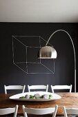 weiße Schale auf rustikalem Holztisch und Bogenlampe vor schwarz getönter Wand mit Würfel-Zeichung