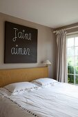 Doppelbett mit Holzkopfteil vor getönter Wand und Bild mit geschriebener Botschaft