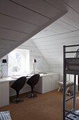 Arbeitstisch mit schwarzen Designer-Drehstühlen am Fenster im Dachzimmer