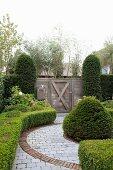 Formgeschnittene Hecken und gepflasterter Weg im Garten mit Holztor