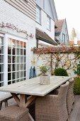 Rattanstühle und rustikaler Holztisch auf Terrasse vor Terrassentür mit Sprossenfenstern