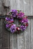 Purple wreath with thistles, radicchio leaves, hydrangea and marjoram flowers on wooden door