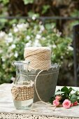 Gas bottle with hand-knitted cover and reel of yarn in metal container on garden table