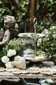 White hydrangeas, hand-sewn hessian sachet & crochet doilies next to cake stand on garden table