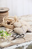 Hand-sewn decorative hearts made from old hessian, parcel string, Chinese scissors and chamomile flowers on old table