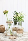 Trim hand-crocheted from jute yarn decorating carafes of flowers