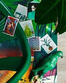 Various photos and artistic parrot figurine on colourful surface with jungle pattern