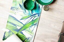 Green ceramic bowls arranged on length of jungle-patterned wallpaper on wooden floor