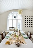 Table festively set in delicate colours; dining room with luster of glass bubbles hanging from vaulted, wooden ceiling and arched window