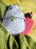 Hot water bottles with handmade covers made from vintage fabric on a green wool blanket