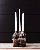 Candles in beer bottles covered in dripped wax with Christmas-tree tag