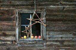 Selbstgebastelte Sterne aus Holzstäben vor adventlichem Fenster mit Äpfeln auf der Fensterbank einer Holzhütte