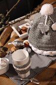 Becher mit Strickbordüre neben selbstgehäkelter Warmhaltehaube und weihnachtliche Deko auf Tisch