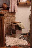 Laundry basket with knitted patchwork cover on bathroom mat and terracotta tiled floor in Mediterranean ambiance