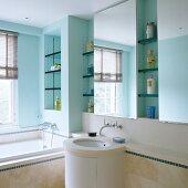 Badezimmer mit türkis getönten Wänden, Regalnischen, Spiegeln und zylinderförmiger Waschtisch
