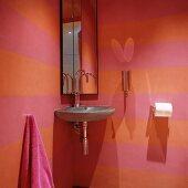 Eckwaschbecken aus Stein und Spiegelschrank in rosa-orange-farben gestreifter Gäste-Toilette