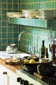 Corner of kitchen - kitchen counter with sink and cooker under shelf of crockery on green-tiled wall
