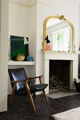 Vintage leather armchair next to open fireplace with gilt-framed mirror