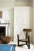 Antique wooden chair in front of white wardrobe next to fireplace in rustic room