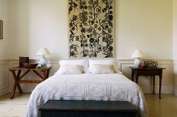 Double bed with lace bedspread below wall panel with floral motif flanked by small bedside tables in simple bedroom