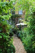 Lush vegetation in garden with gravel path leading to house with brick facade